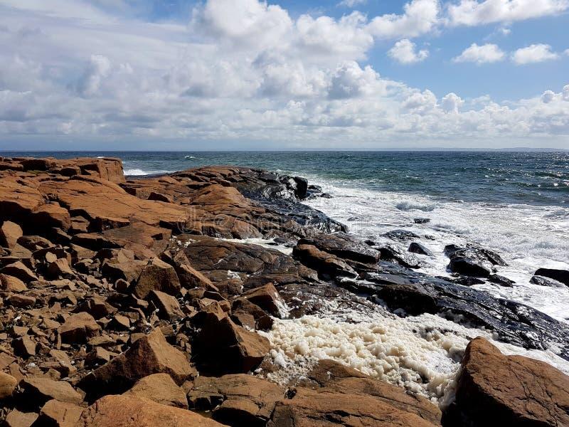 Vagues frappant les falaises rougeâtres dans le vent par jour ensoleillé sur le Westcoast de la Suède, Halmstad images stock