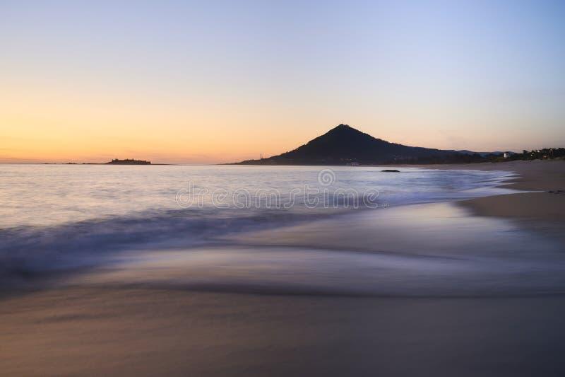 Vagues lisses au-dessus d'une plage sablonneuse au coucher du soleil avec la montagne à l'arrière-plan photos libres de droits