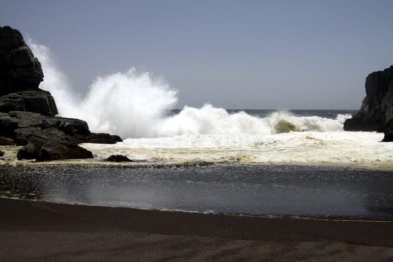 Vagues puissantes se brisant sur une roche et éclaboussant l'eau dans le ciel sur la plage noire à distance de sable de lave à la images libres de droits