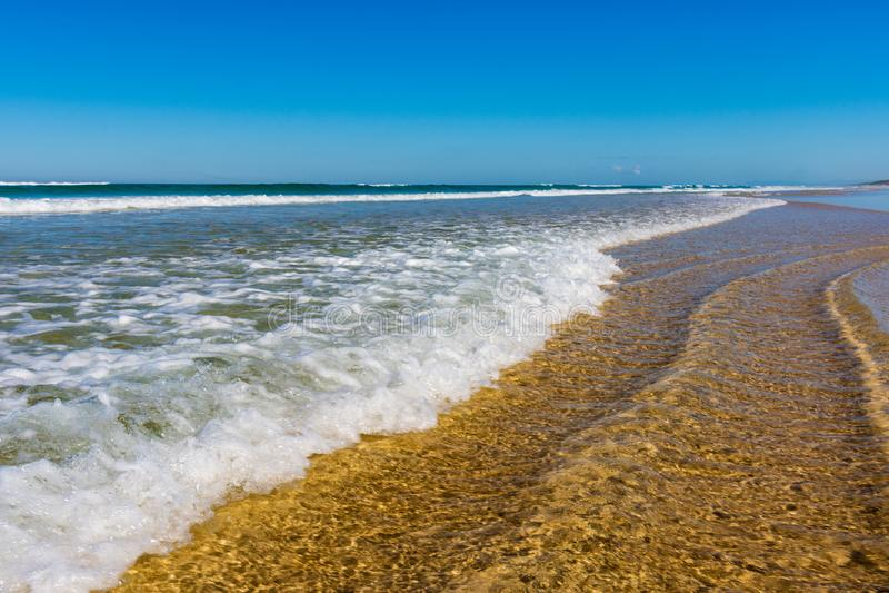 Vagues roulant dedans sur la plage images stock