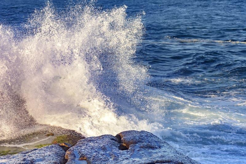 Vagues se brisant contre des roches avec le jet d'eau photographie stock libre de droits