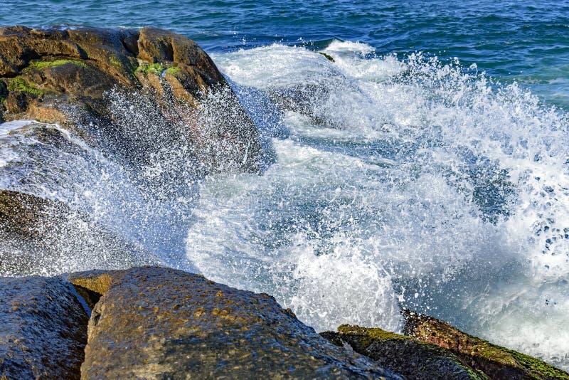 Vagues se brisant contre des roches avec le jet d'eau image stock