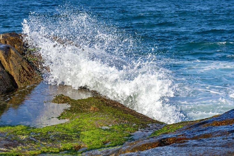 Vagues se brisant contre des roches avec le jet d'eau photographie stock