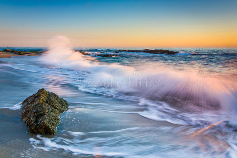 Vagues se brisant sur des roches au coucher du soleil, chez Victoria Beach photo libre de droits