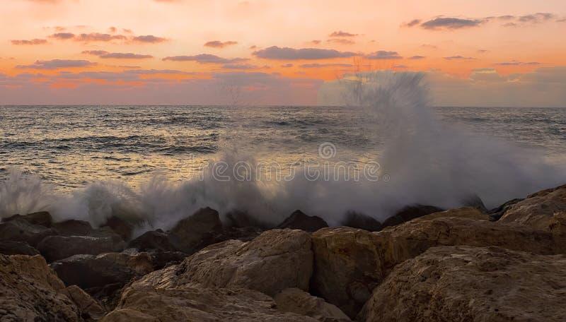 Vagues se brisant sur des roches au coucher du soleil photo stock
