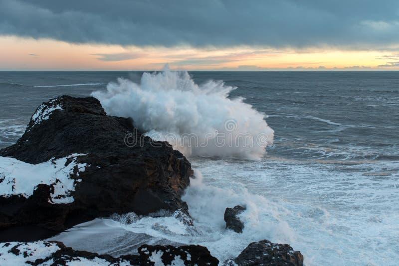 Vagues se brisant sur des roches en Islande image libre de droits