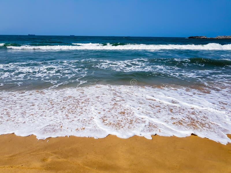 Vagues se brisant sur la plage, avec la mousse de mer blanche sur le sable Scène tropicale de plage, beau temps images libres de droits
