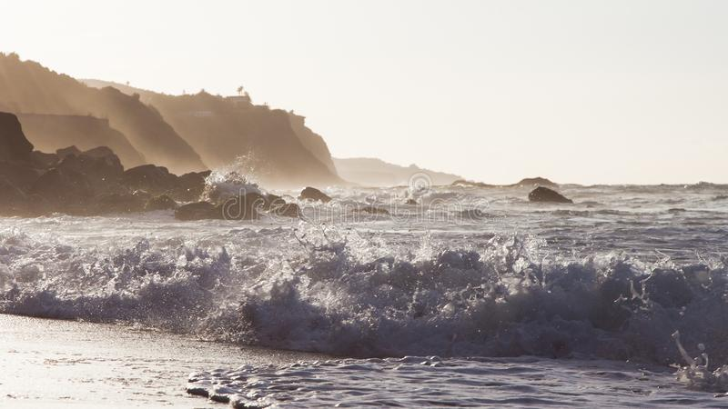 Vagues se cassant sur le rivage d'une plage de Ténérife avec la lumière arrière du coucher du soleil approchant images stock