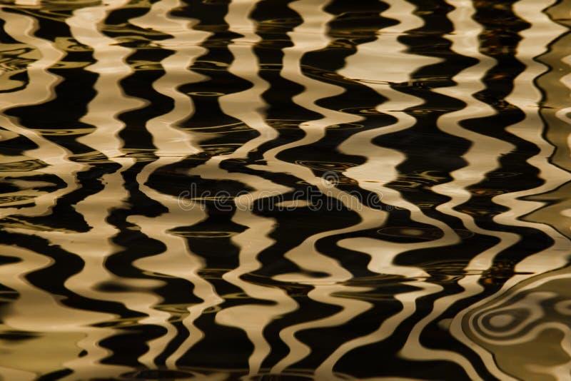 Vagues sur l'eau formant des rayures semblables à la texture du velours, l'alternance de l'or et rayures et vagues noires photo libre de droits