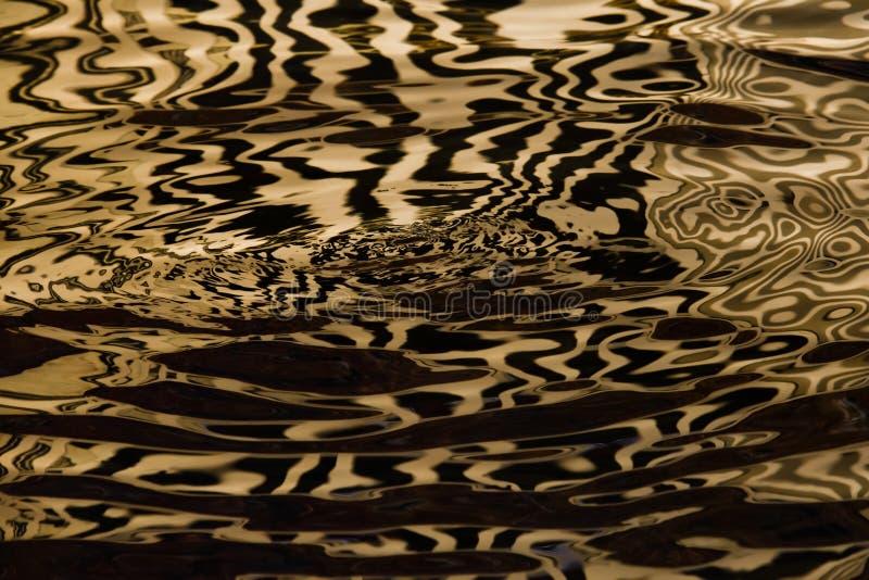 Vagues sur l'eau formant des rayures semblables à la texture du velours, l'alternance de l'or et rayures et vagues noires photographie stock libre de droits
