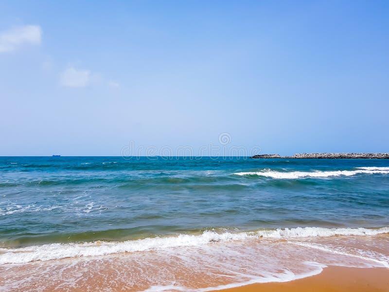 Vagues sur une plage sablonneuse L'eau bleue et cieux clairs - mousse de mer blanche sur le sable Fond de bord de la mer de natur photographie stock libre de droits