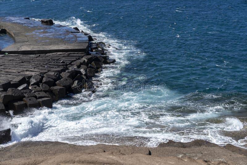 vagues turbulentes de la coupure d'océan dans une traînée de pierre photos stock