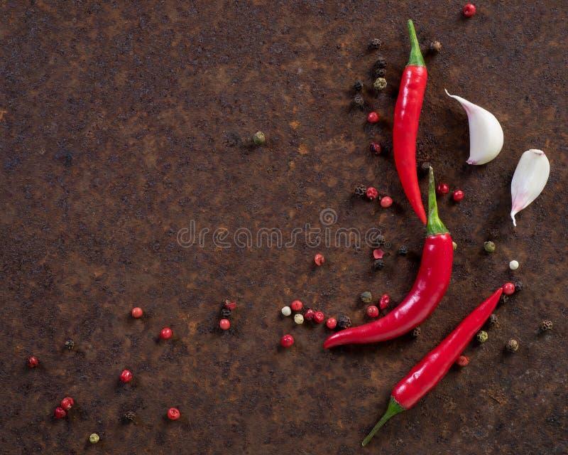 Vainas y guisantes candentes, clavo de la pimienta de chile de ajo en m oxidado oscuro foto de archivo libre de regalías