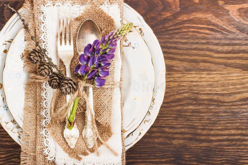Vaisselle avec les lupines et l'argenterie violets photo libre de droits