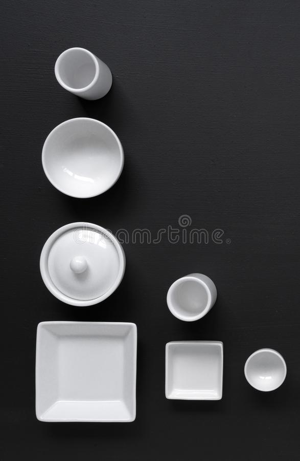 Vaisselle blanche et moderne dans diverses conceptions sur un fond noir photo stock