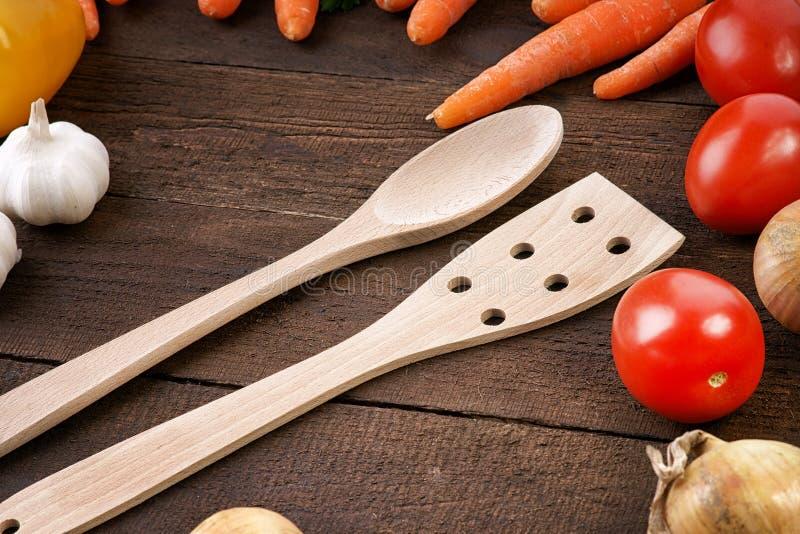 Vaisselle de cuisine en bois avec des légumes sur un fond en bois image stock