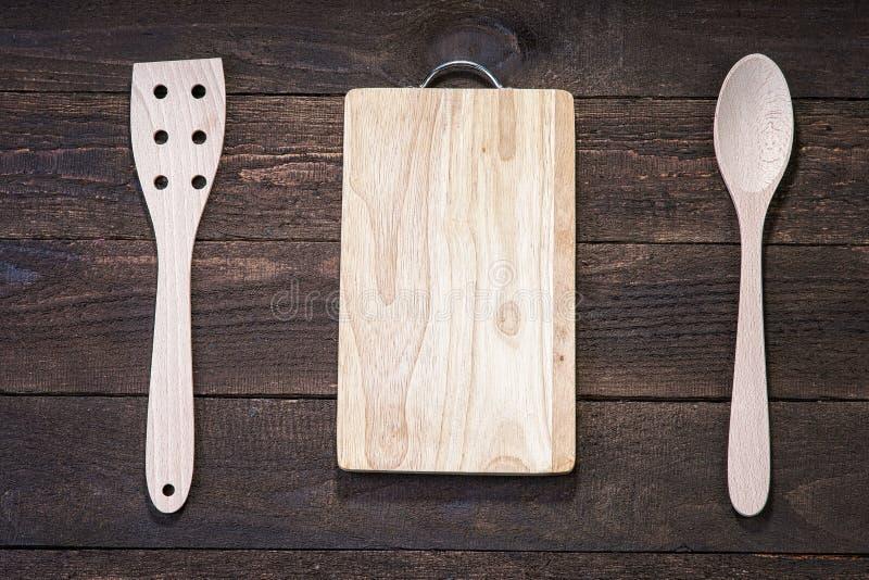 Vaisselle de cuisine et planche à découper en bois sur la table en bois photos stock
