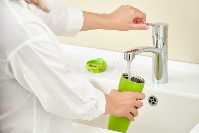 Vaisselle de femme pour laver une bouteille de thermos image stock
