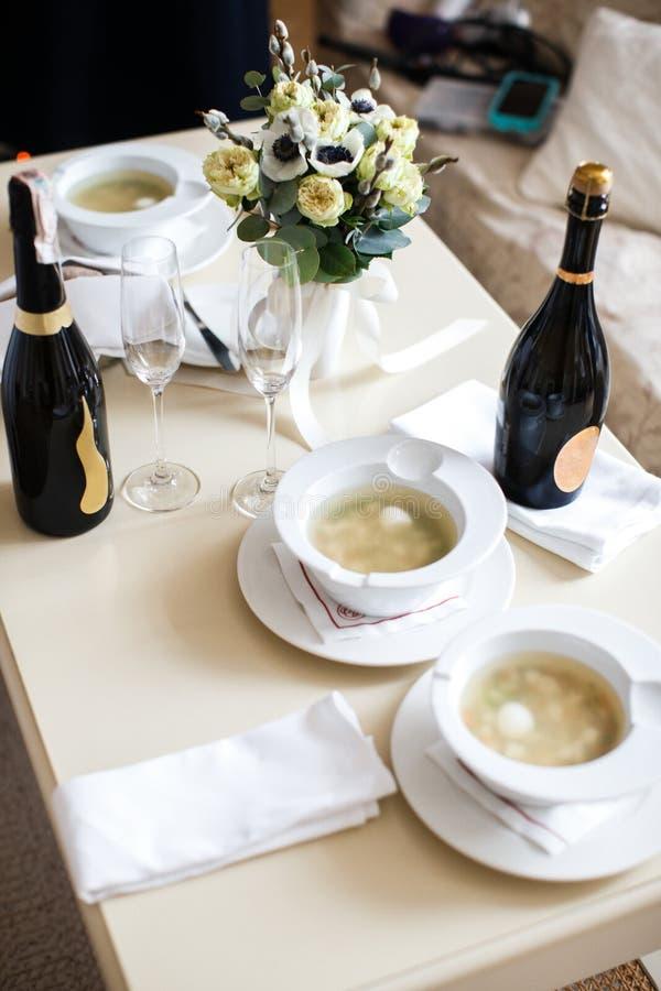 Vajilla de cerámica en la tabla y y dos botellas de champán foto de archivo libre de regalías
