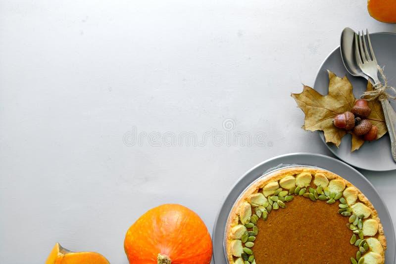 Vajilla, pastel de calabaza hecho en casa, calabaza y bellotas en fondo de madera gris fotografía de archivo