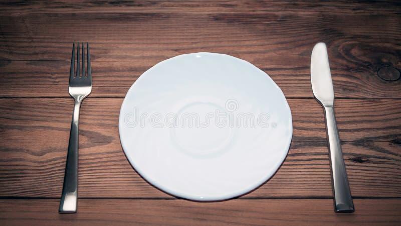Vajilla: Placa blanca vacía, bifurcación de acero y cuchillo en la tabla de madera rústica Visión superior con el espacio del tex foto de archivo libre de regalías