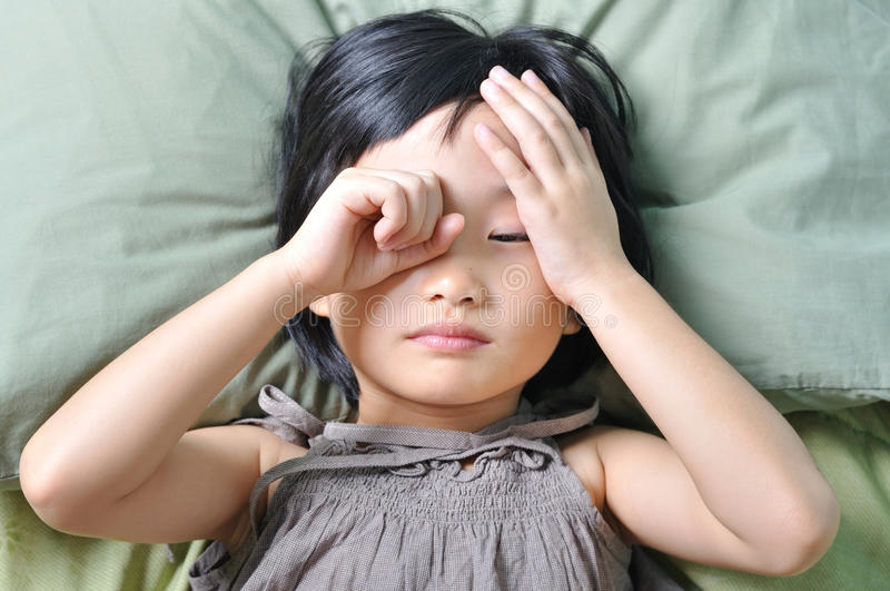 Vak upp av det sömniga asiatiska lilla barnet arkivfoton
