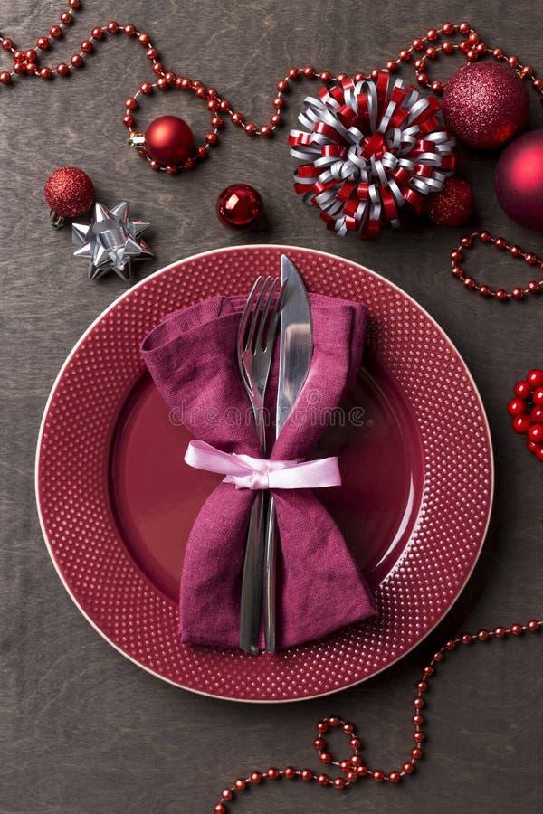 Vakantie die rode plaat met vork en mes, servet met rond boog, Kerstmisspeelgoed dienen royalty-vrije stock fotografie