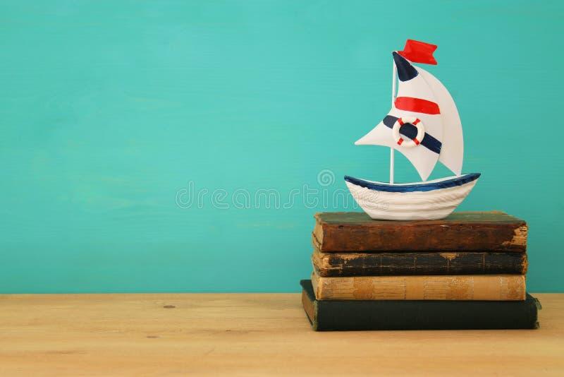 Vakantie en de zomerbeeld met boot en antieke boeken over houten lijst royalty-vrije stock afbeelding