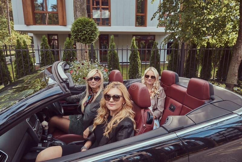 Vakantie en mensenconcept Drie blonde vrouwelijke vrienden die modieuze kleren in zonnebril dragen die in a zitten stock fotografie
