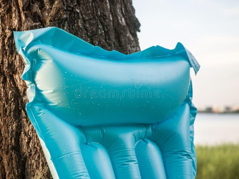 Vakantie en recreatieconcept De opblaasbare blauwe strandmatras voor het zwemmen met dalingen van water leunde tegen een boom stock foto