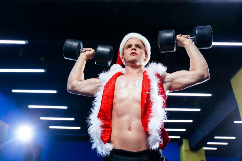 Vakantie en vieringen, Nieuw jaar, Kerstmis, sporten, het bodybuilding, gezonde levensstijl - Spier knappe sexy Kerstman stock afbeeldingen