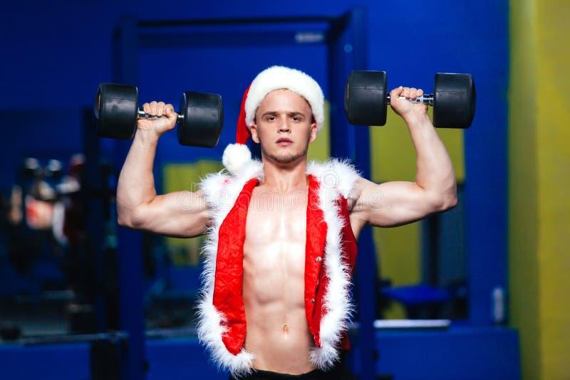 Vakantie en vieringen, Nieuw jaar, Kerstmis, sporten, het bodybuilding, gezonde levensstijl - Spier knappe sexy Kerstman stock foto's