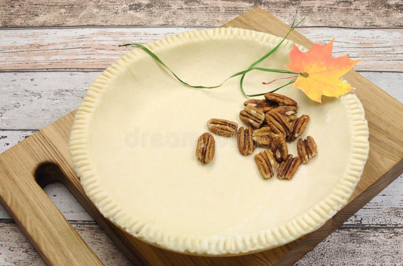 Vakantie feestelijk baksel met een lege pasteishell gebakjekorst met ruwe pecannootnoten stock afbeeldingen