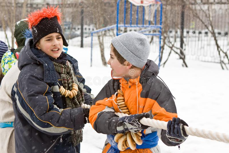 Vakantie Maslenitsa De wintersneeuw Kinderen met donuts Touwtrekwedstrijd 2 royalty-vrije stock fotografie