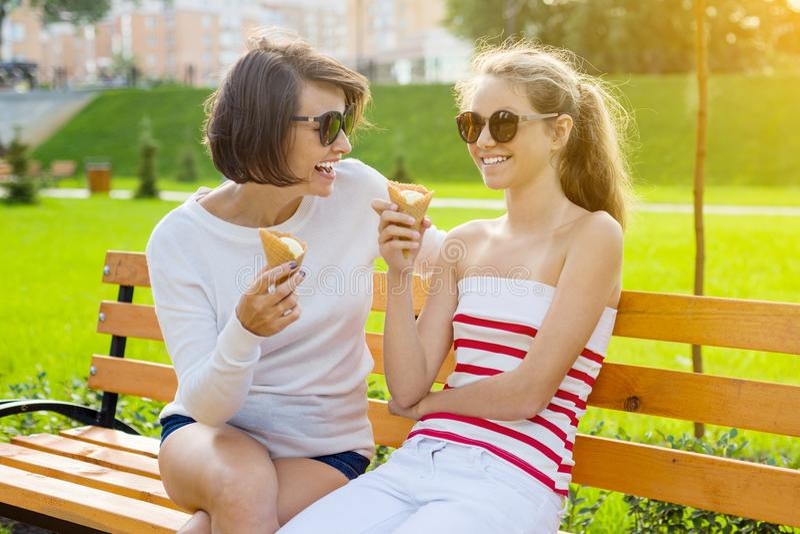 Vakantie met de familie Gelukkige jonge moeder en leuke dochtertiener die in stadspark roomijs, het spreken en het lachen eten stock afbeeldingen