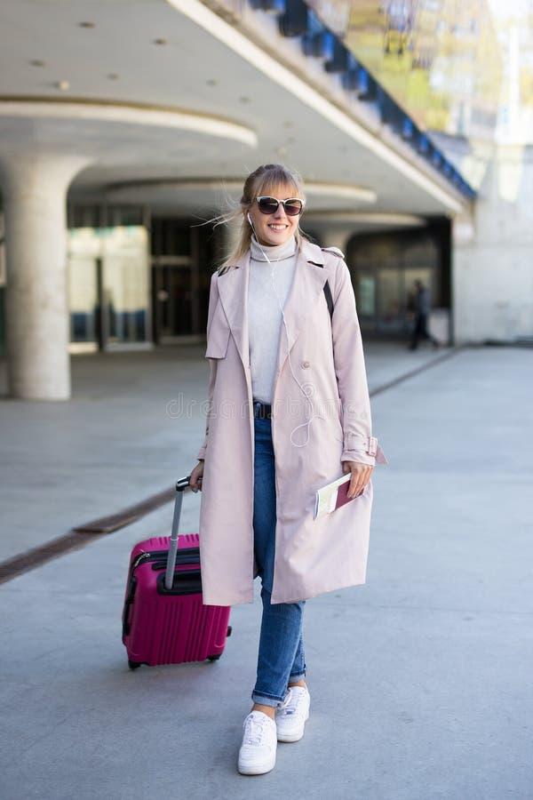 Vakantie, toerisme en reisconcept - jonge vrouwentoerist die met koffer in luchthaven of post lopen royalty-vrije stock afbeelding
