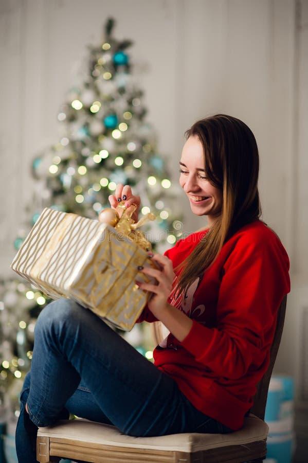 Vakantie, viering en mensenconcept - glimlachende vrouw rode sweather dragen en jeans die gouden giftdoos uitstellen stock afbeelding