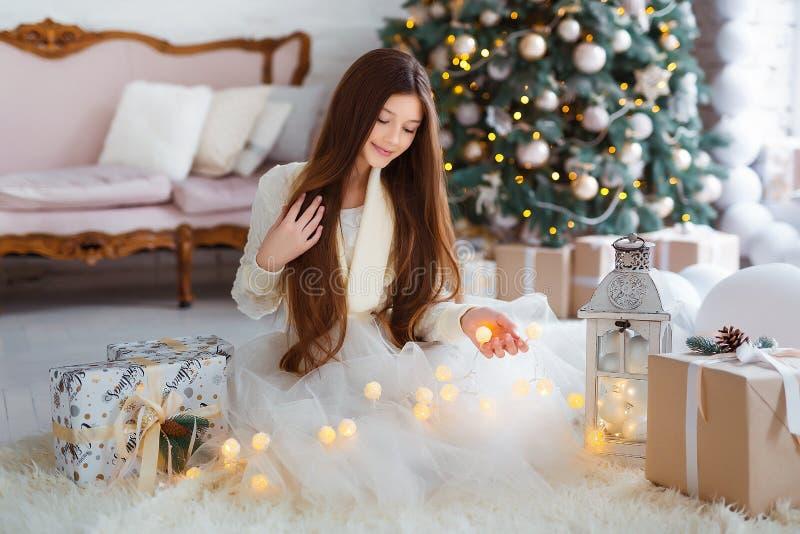 Vakantie, viering en mensenconcept - Portret van mooi meisje met lang haar die warme de winterkleren binnen dragen stock fotografie
