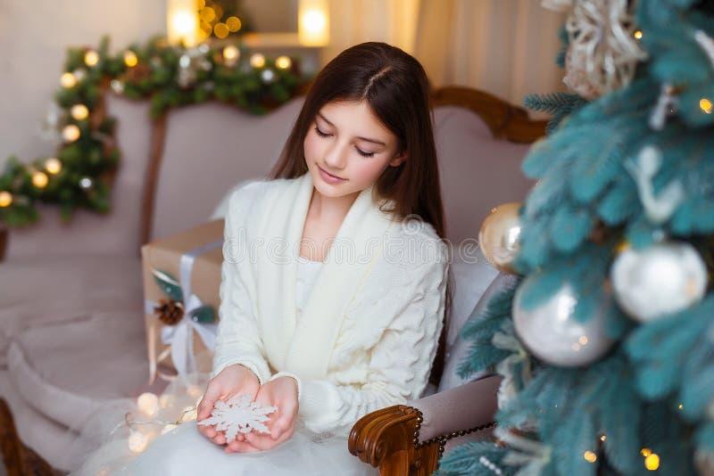 Vakantie, viering en mensenconcept - Portret van mooi meisje met lang haar die warme de winterkleren binnen dragen royalty-vrije stock afbeelding