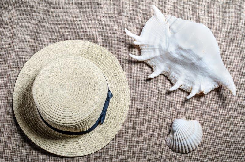 Vakantie vlakke mening met overzeese shellsseashells van de strohoed en stock foto