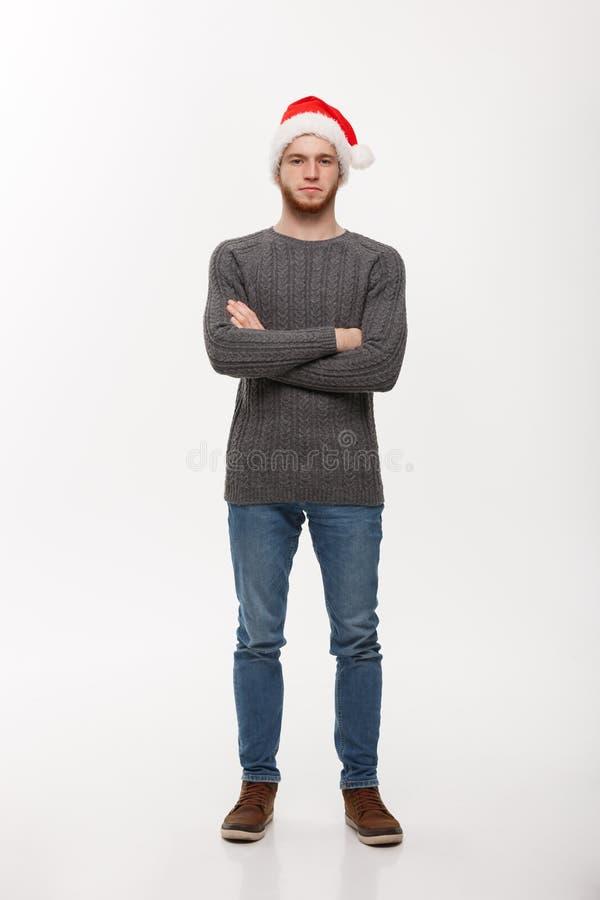 Vakantieconcept - de Jonge baardmens in sweater kruiste wapens die op witte achtergrond stellen stock fotografie