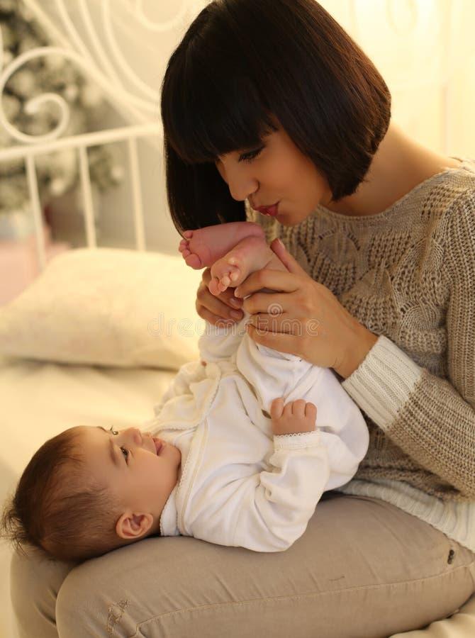 Vakantiefoto het mooie moeder stellen met haar leuke kleine baby royalty-vrije stock afbeelding