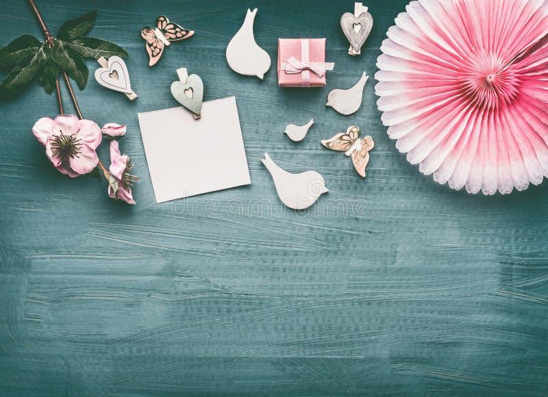 Vakantielay-out met bloemen, decoratieve vogels, roze giftvakje, lege document kaartspot omhoog en partijventilator royalty-vrije stock foto