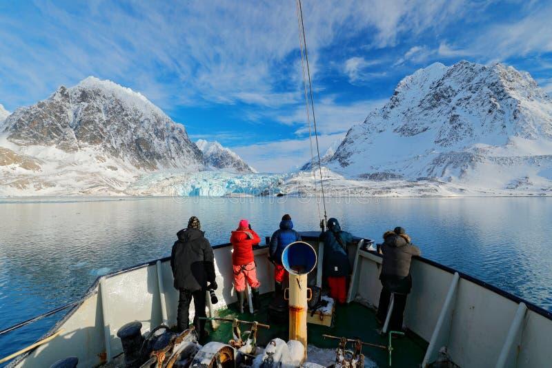 Vakantiereis in het Noordpoolgebied, Svalbard, Noorwegen Mensen op de boot De winterberg met sneeuw, blauw gletsjerijs met overze stock foto