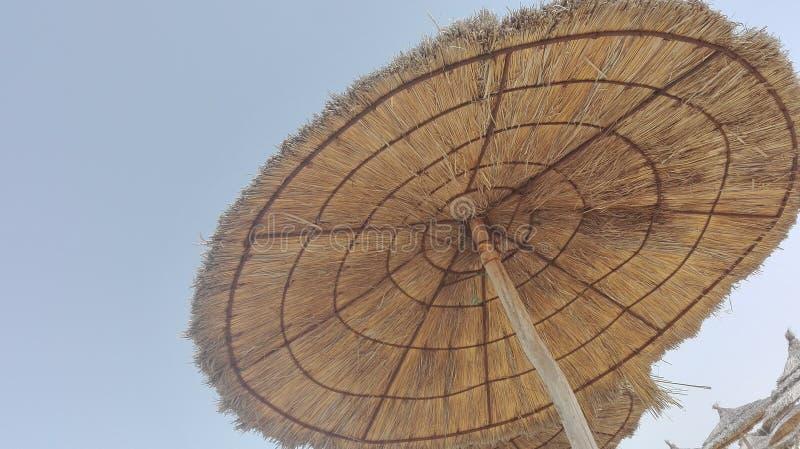 Vakantiethema's - een paraplustro op blauwe wolkenloze hemel stock fotografie