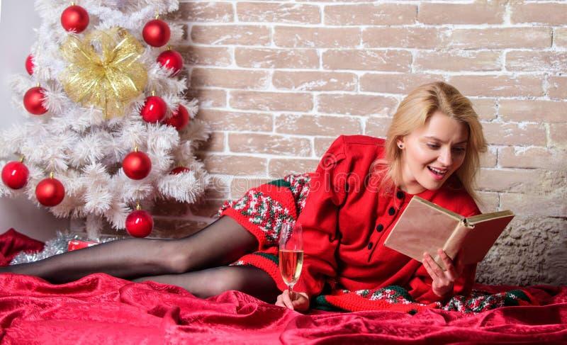 Vakantieuiteinden voor introvert Vier Kerstmis zonder sociale verplichtingen Het glaschampagne en boek van de vrouwengreep Meisje royalty-vrije stock afbeeldingen
