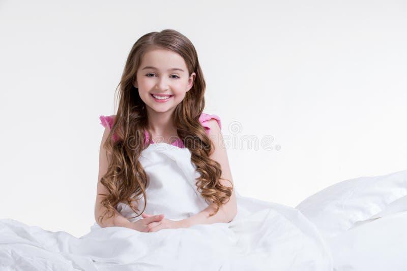 Vaken lycklig liten flicka och sammanträde i sängen. fotografering för bildbyråer