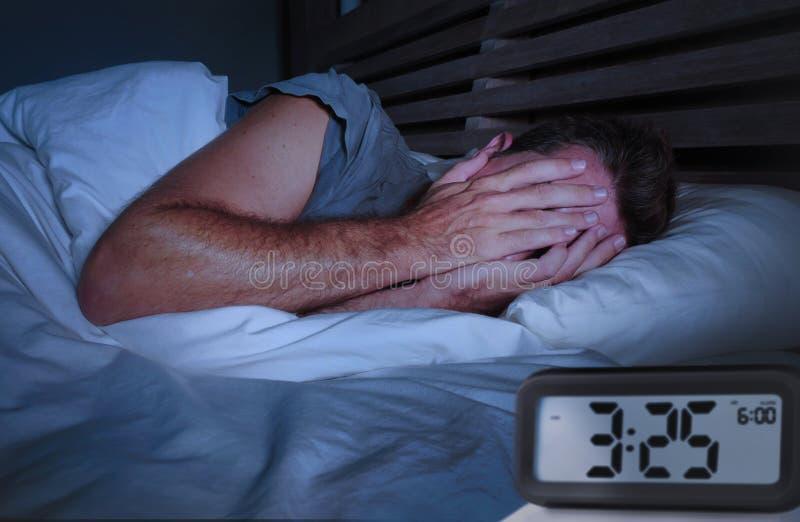 Vaket ligga för ledsen man som är sömnlöst på sängbeläggning hans ögon som gråter lidandesömnlöshet som sover oordning med ringkl fotografering för bildbyråer
