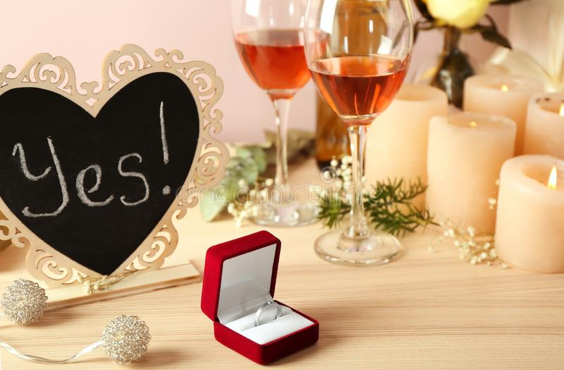 Vakje met verlovingsring met glazen van wijn en kaarsen houten lijst stock foto