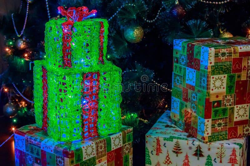 Vakjes met Kerstmisgiften in kleurrijk die document met lichtgevende slingers wordt verfraaid royalty-vrije stock foto